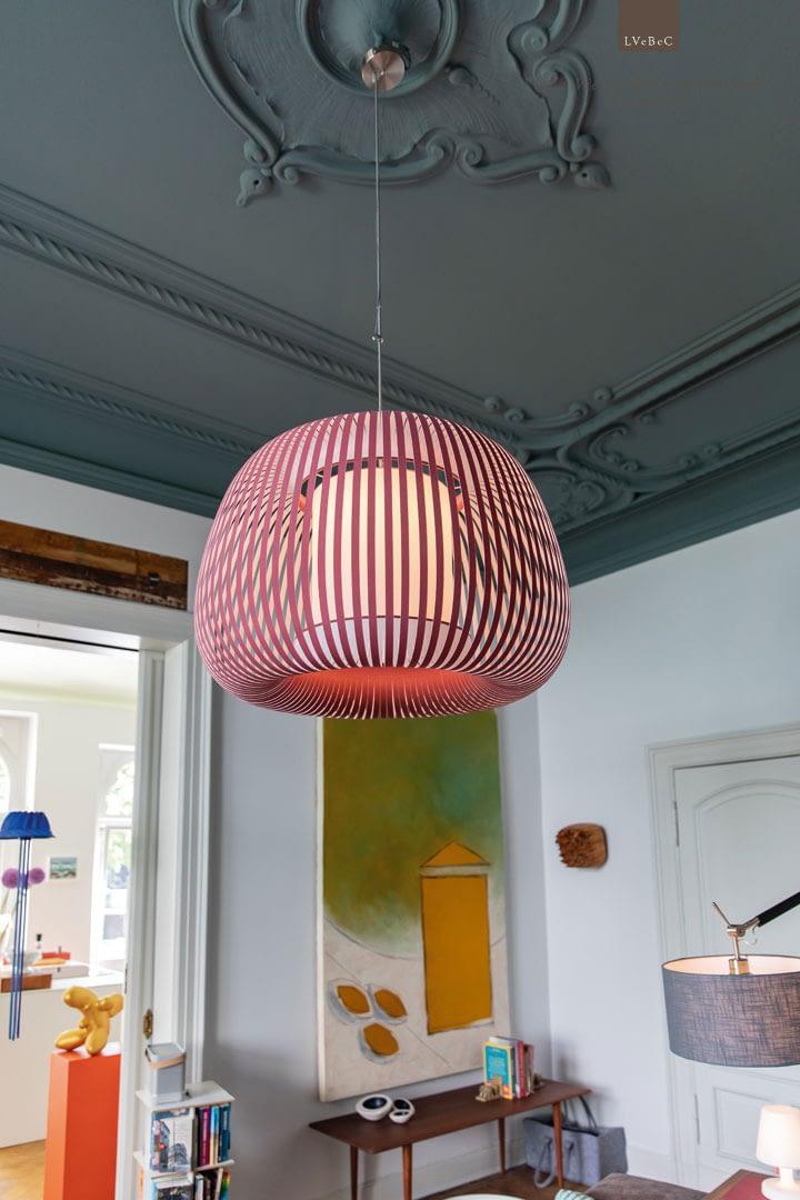 Farbkonzept dunkelblauer Stuckdecke Wohnzimmer mit rosa Deckenleuchte und Blick in die Kueche