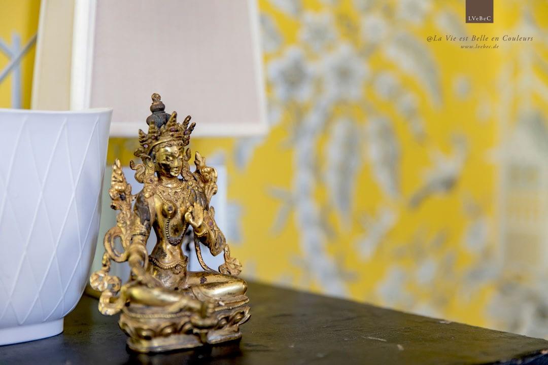 Asiatische Skulptur von gelber, gemusterter Tapete