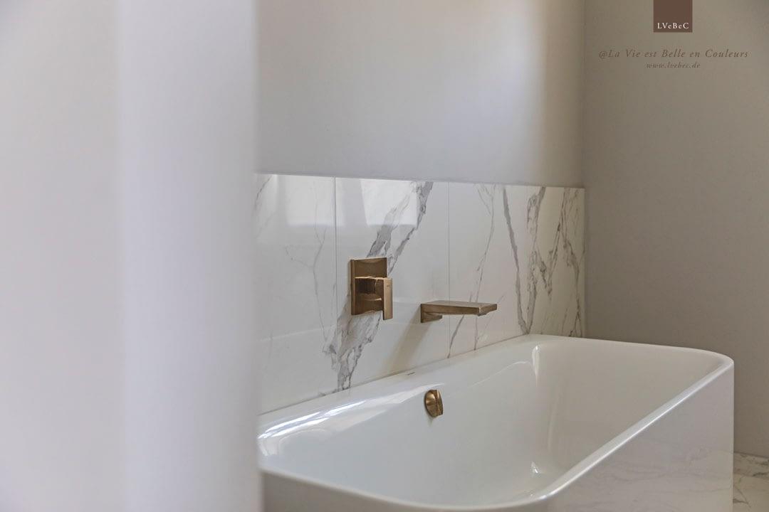 Farbkonzept Badezimmer mit Marmor und hellgrauen Wänden und kupferfarbenen Armaturen