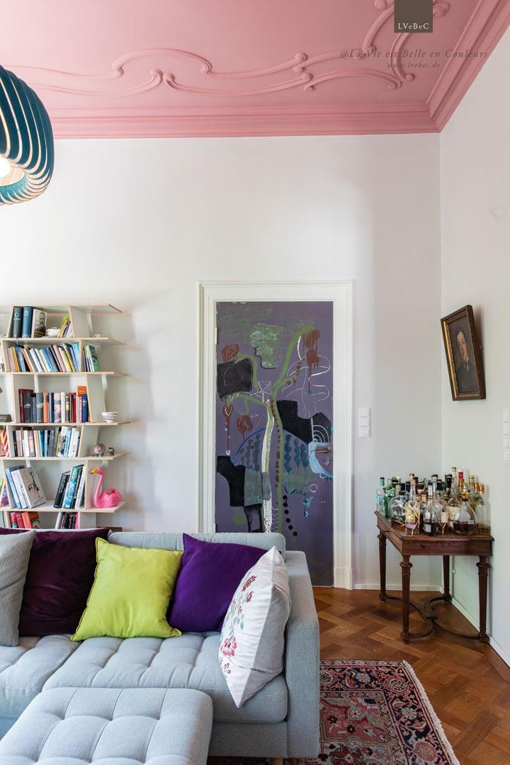Salon Stuckdecke in Rosarot mit kunstvoller Zimmertuer und Moormann Bücherregal