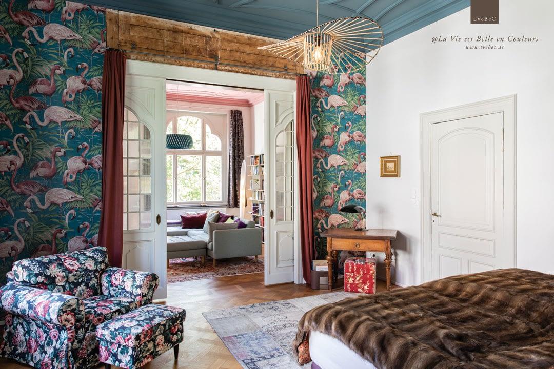 Schlafzimmer mit Tapete und Moebeln im Mustermix