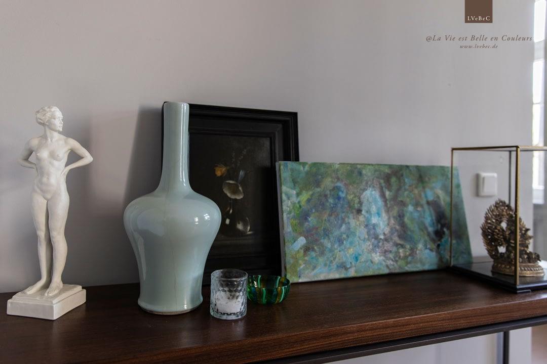 Dekoration mit Vasen und Bildern vor hellgraue Wand auf einem Sideboard
